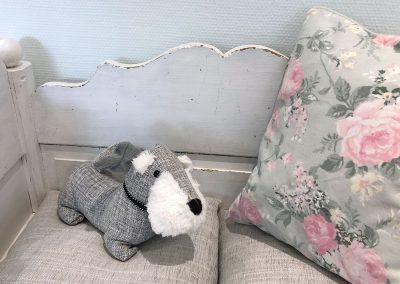 Sitzbank mit Rosenkissen und Stoffhund