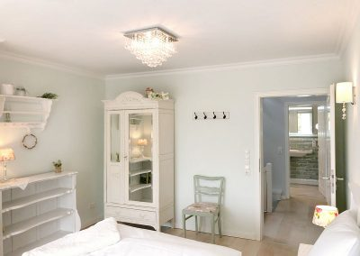 Schlafzimmer mit weißen Möbeln im Shabby Chic
