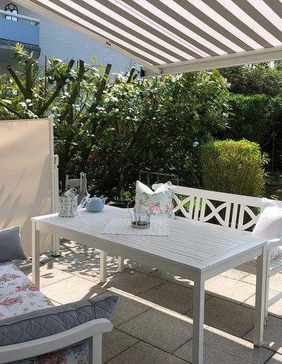 Gemütliche Sitzecke auf Gartenterrasse mit Sonnendach