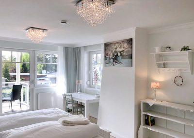 Schlafzimmer mit kleinem Schreibtisch und Balkon