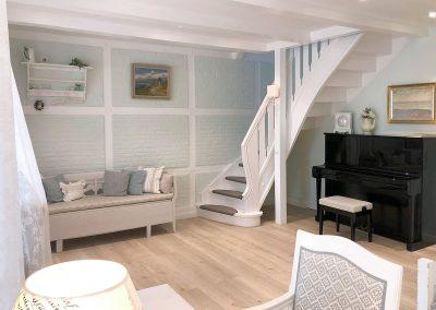 Wohnbereich mit Sitzbank, Schreibtisch und Klavier