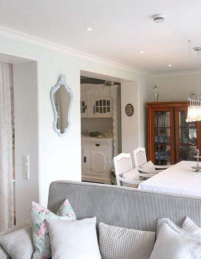 Wohnbereich: Couch mit vielen romantischen Kissen, großem Esstisch, Vitrinen und mehr