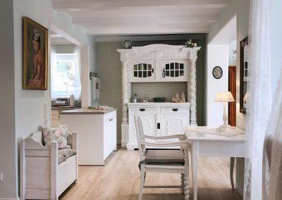 Blick in Teil des Wohnbereiches: Schreibtisch, Sitzbank, rustikaler Küchenschrank, alles im Chabby Chic