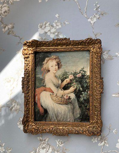 Frau mit Blumenkorb auf Bild mit Goldrahmen an Wand mit Blütentapete