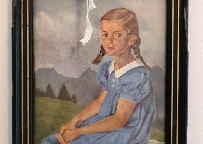 Kleines Mädchen mit Zöpfen vor Berglandschaft, Bildrahmen mit Schleife