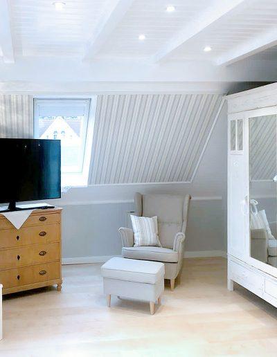 Sitzmöbel, TV und weißer romantischer Kleiderschrank